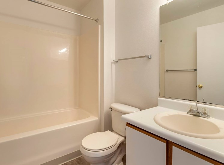 Bathroom with mirror above sink and towel rack. Bath tub and white countertops