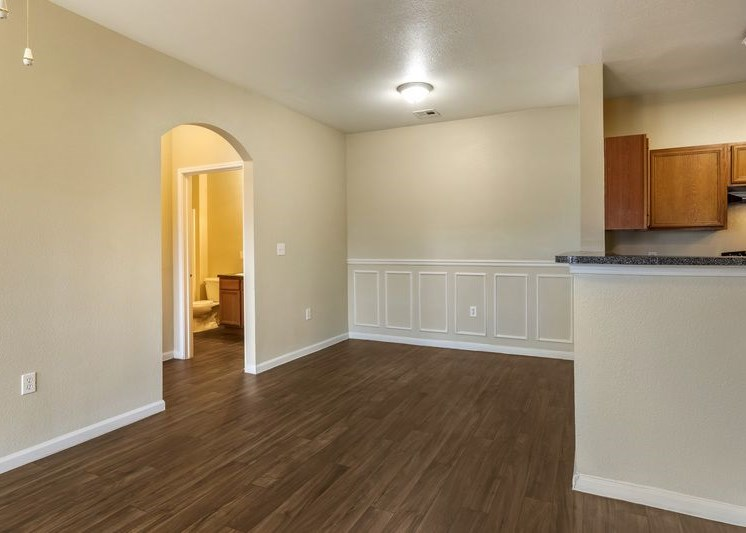 Dining room with hardwood style flooring, arched entry ways, and white trim