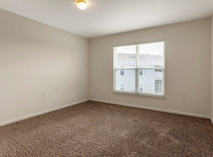 bedroom with wall to wall carpet and a large window.