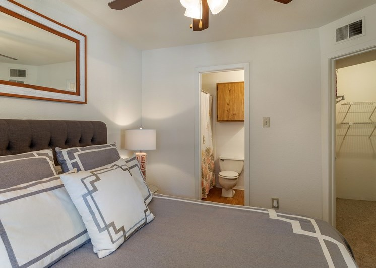 Decorated bedroom with full-size bed, gray and white color scheme, and a view of the bathroom
