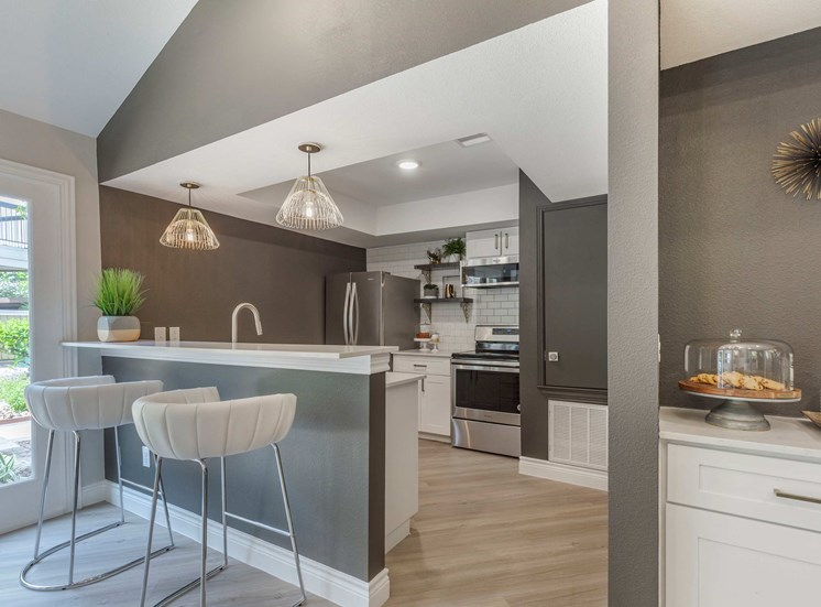 Clubhouse Kitchen with Breakfast Bar Stainless Steel Appliances White Cabinets and Bar Stools