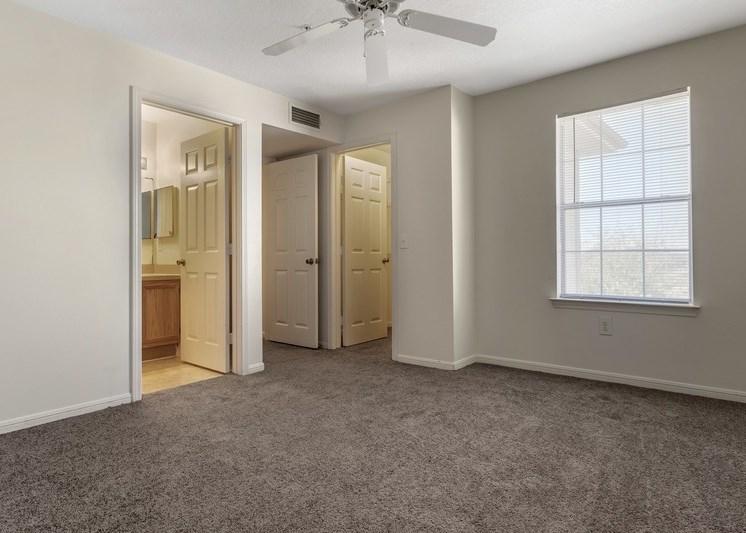 Bedroom with en-suite bathroom, ceiling fan, and carpet flooring