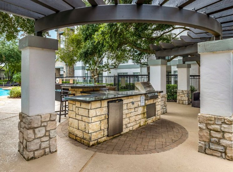 Poolside gas grilling stations with picnic seating and lounge chairs