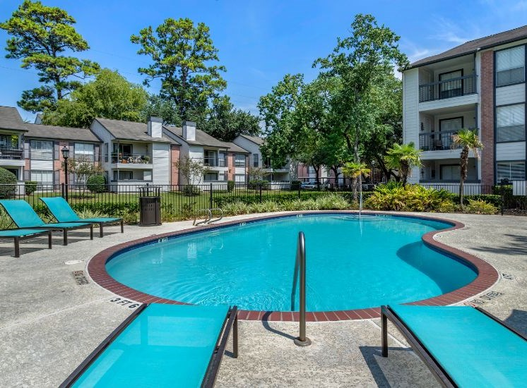 Swimming pool with tanning deck, large green trees, and apartment building exterior in the background