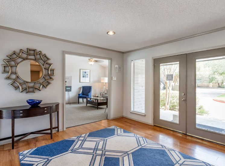 Clubhouse interior with hardwood style flooring, blue and cream rug, and a mirror hanging on the wall