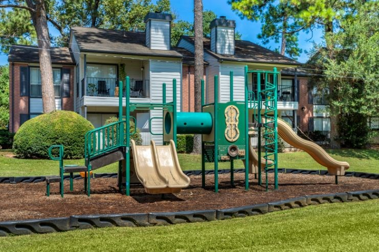 Playground with green and yellow color scheme and apartment building exterior in the background