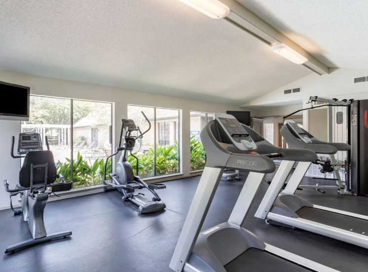Fitness center with treadmills, large windows, and a spinning machine