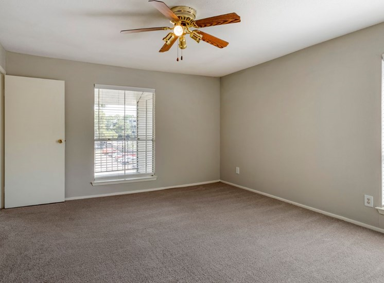 Living room with ceiling fan, white walls, and tan carpet