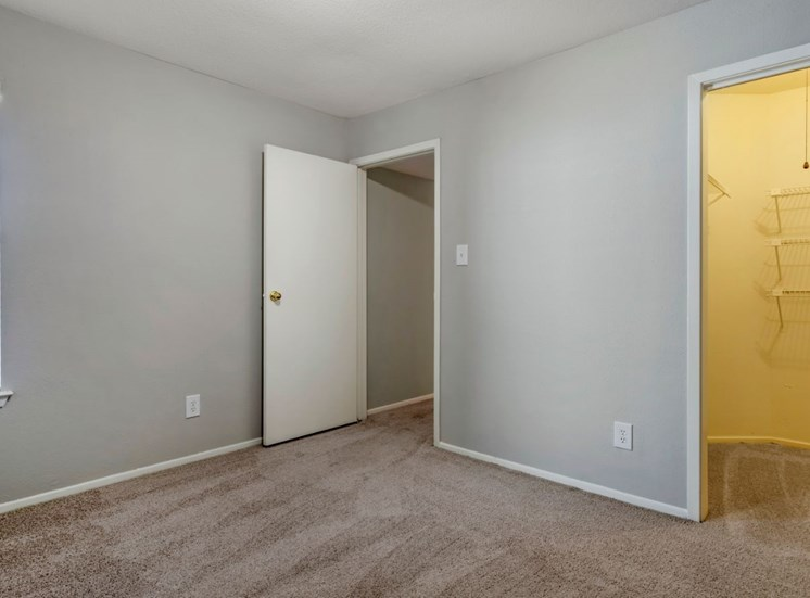 Bedroom with gray walls, white trim, and tan carpet
