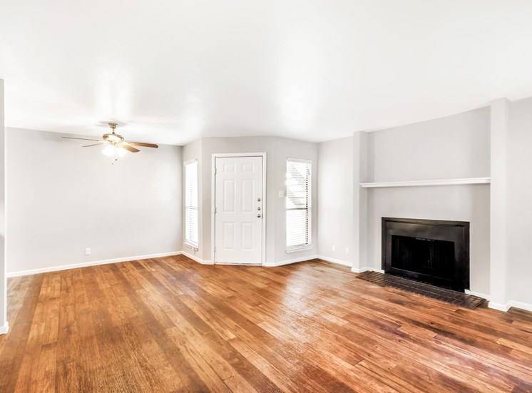 Living room with fireplace, hardwood style flooring, and ceiling fan