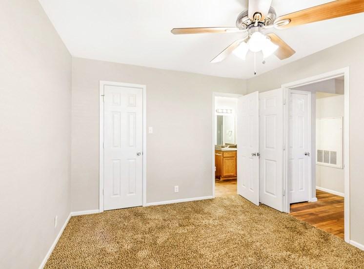 Bedroom with ensuite bathroom, closet door and Ceiling fan