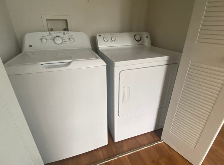 Laundry Room with double door folding doors and  full size side by side washer and dryer