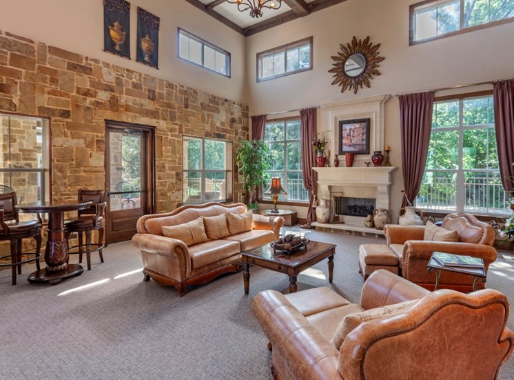 Clubhouse interior with tall ceilings, gray carpet, and tan and brick walls. Decorative furniture is a coral color with accent pillows and windows alongside the perimeter of the room.