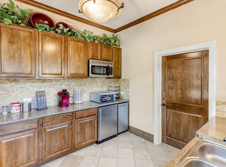 Clubhouse kitchen with abundant wooden cabinets, stainless steel built in microwave, and a double basin sink