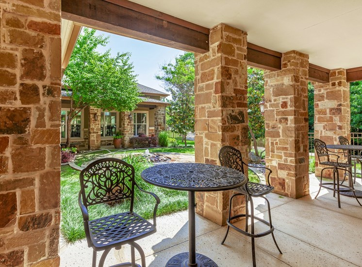 Clubhouse outdoor patio seating, four brick pillars, high top tables with chairs, and lush green grass and trees in the background