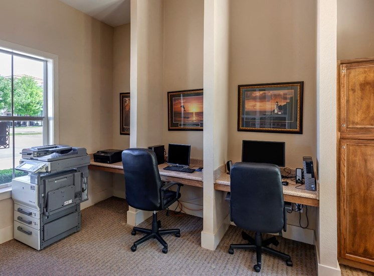 Business center with computers, rolling gray chairs, photos on the wall, light gray carpet, and a printer.