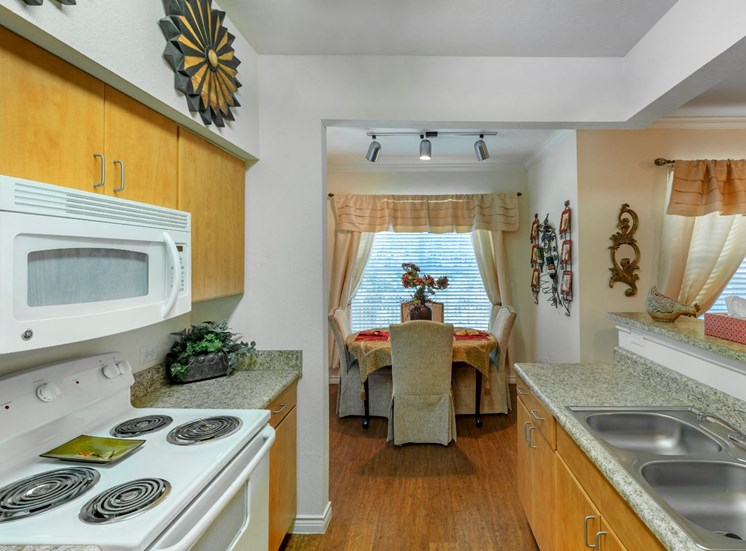 Kitchen with double basin sink, built in microwave, and wooden cabinets along the top and bottom areas of the kitchen