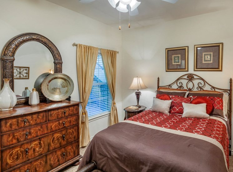 Bedroom with full-size bed, a color scheme of reds and gold with two photos hanging above the bed and a wooden dresser located near the foot of the bed. A window that peeks out to the stairwell is also located to the left of the bed.