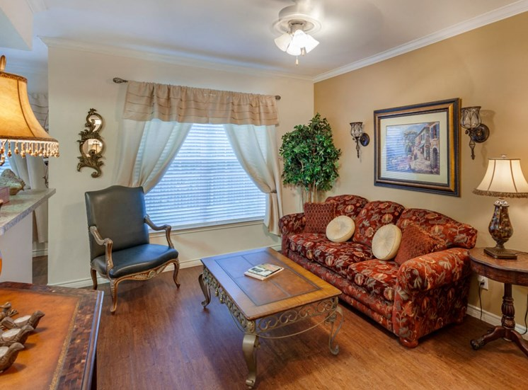 Decorated living room with curtains, couch, framed painting hanging above the couch, and a coffee table. Photo also includes an accent wall directly behind the couch that is a light tan/yellow color and hardwood style floors.