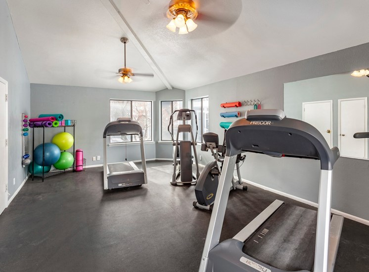 Fitness center with cardio equipment, multi speed ceiling fan, and windows for natural lighting