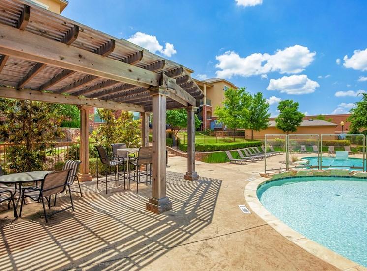 Pergola with table and chairs next  the swimming pool.