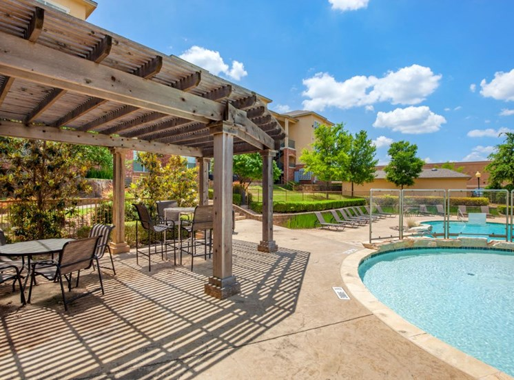 Sparkling blue swimming pool, wooden pergola, and patio tables and chairs with green trees in the far background