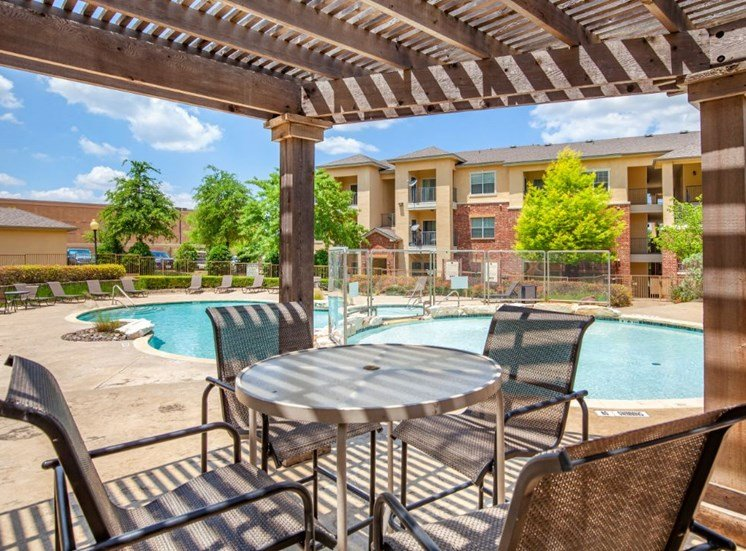 Sparkling blue swimming pool, pergola with table and chairs, apartment building and green trees in the background