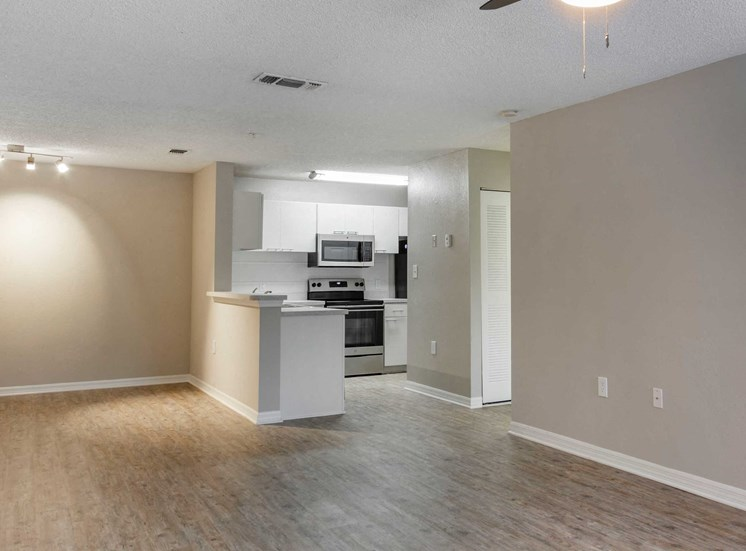 Open Floor Plan with Breakfast Bar off Kitchen with White Cabinets Grey Counters and Stainless Steel Appliances