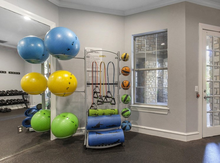 Fitness Center with Exercise Equipment  Next to Mirror Accent Wall