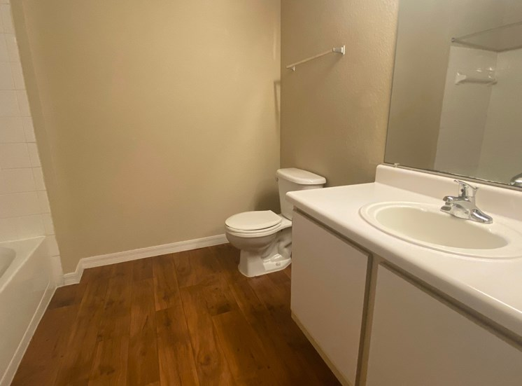 Bathroom featuring, wood flooring white countertop vanity , toilet, and tub with tile back splash, towel bar, and mirror