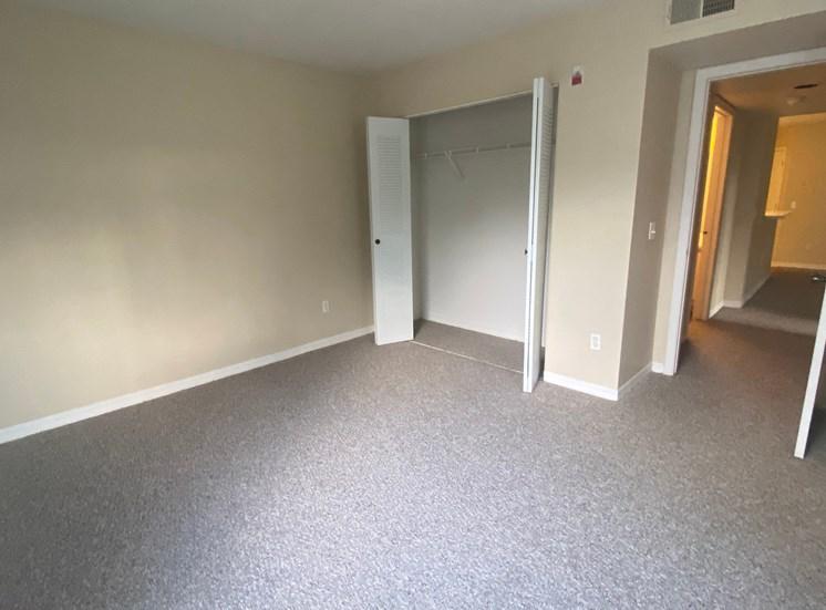 Carpeted bedroom with double door closet, double tone paint and bedroom door leading to hall