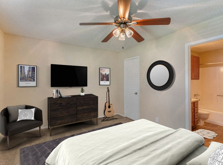 bedroom with ceiling fan mounted television en suite bedroom and an accent chair