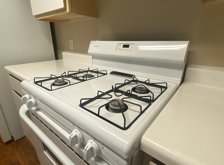 Kitchen with white gas stove, white counter tops, white cabinet faces, and white refrigerator