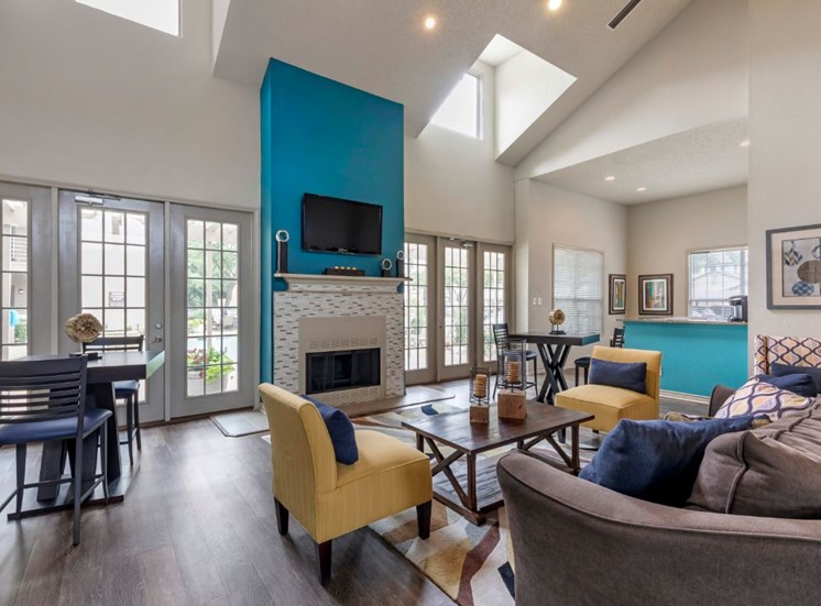 Clubhouse interior with teal accent walls mustard yellow accent chair sky lights and hardwood style flooring
