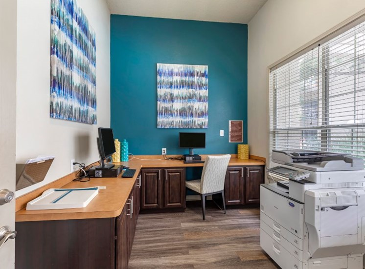 Business center with teal accent wall two computers and a printer