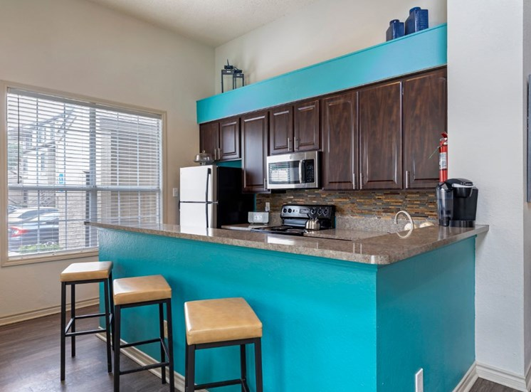 Clubhouse kitchen with teal accent walls wooden style cabinetry that is espresso colored and hardwood style flooring