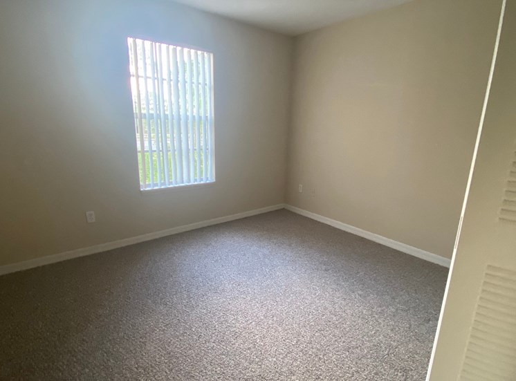 Carpeted Guest Bedroom with one window, and closet to the right of front door