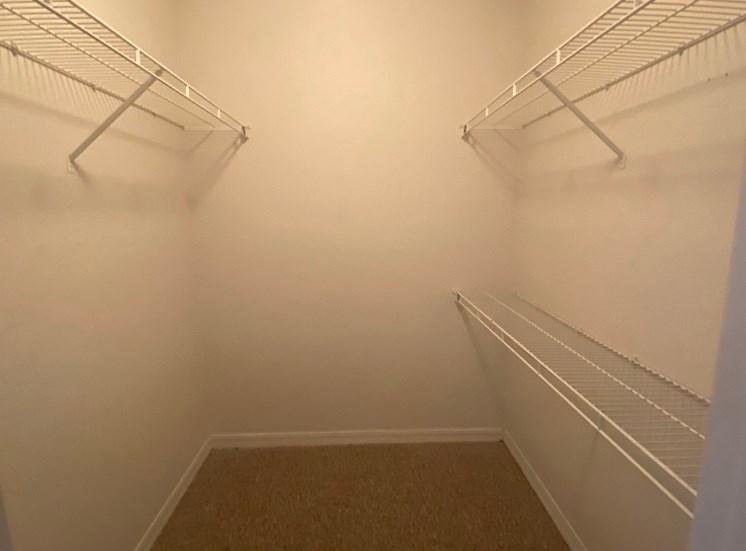 Spacious single door closet with mounted metal shelves
