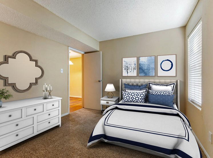 Furnished Bedroom with a bed decorated with white linens, white dresser, mirror, and framed photos