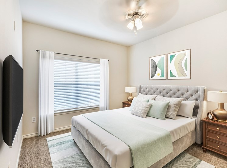 Bedroom with bed night stands , large window with ceiling fan