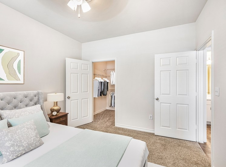Bedroom with queen size bed, night stand with lamp next to closet door