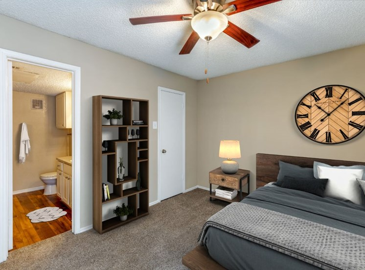 Virtual rendering of bedroom with ceiling fan, gray and white blankets, and an en suite bathroom