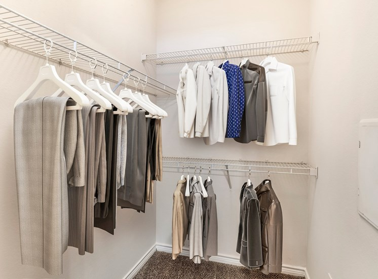 Closet with wire shelves and clothes hanging from them.