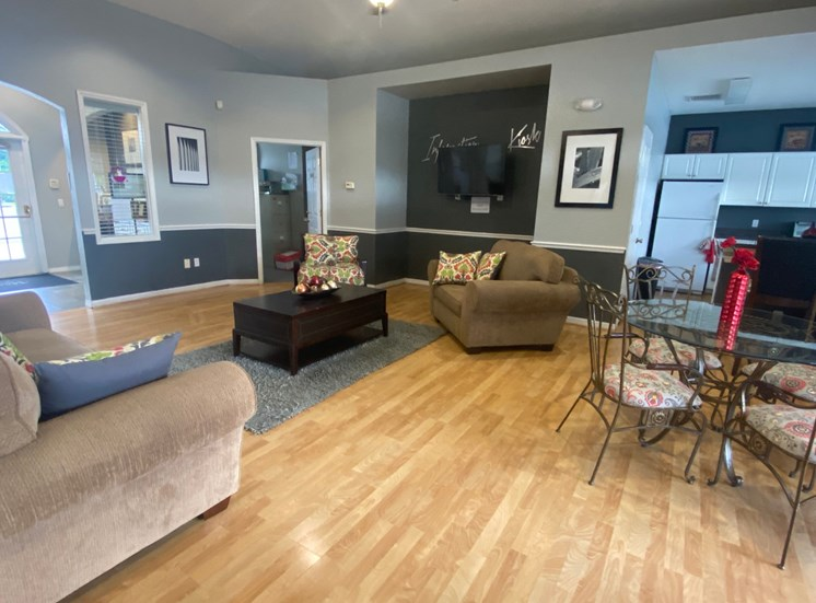 Clubhouse interior with love seat and arm chair, hardwood style flooring, glass table and chairs, and kitchen in the background