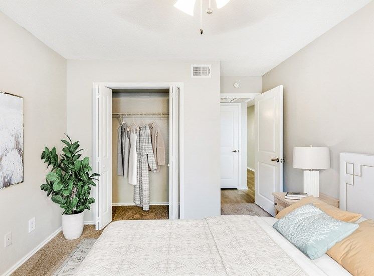 Bedroom with bed, closet, picture on wall and plant in corner with nightstand.