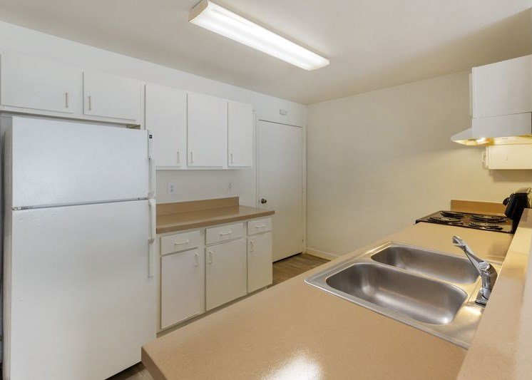 Fully equipped kitchen with double basin sink, white cabinets, and white refrigerator