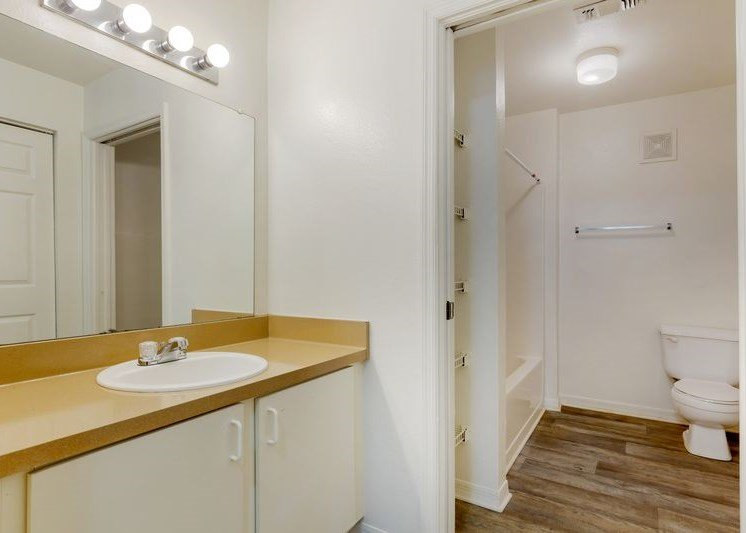 Bathroom with white walls, oversized mirrors, and closet space