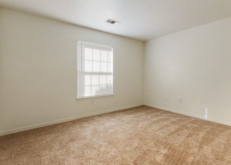 Bedroom with tan carpet, white walls, and a window