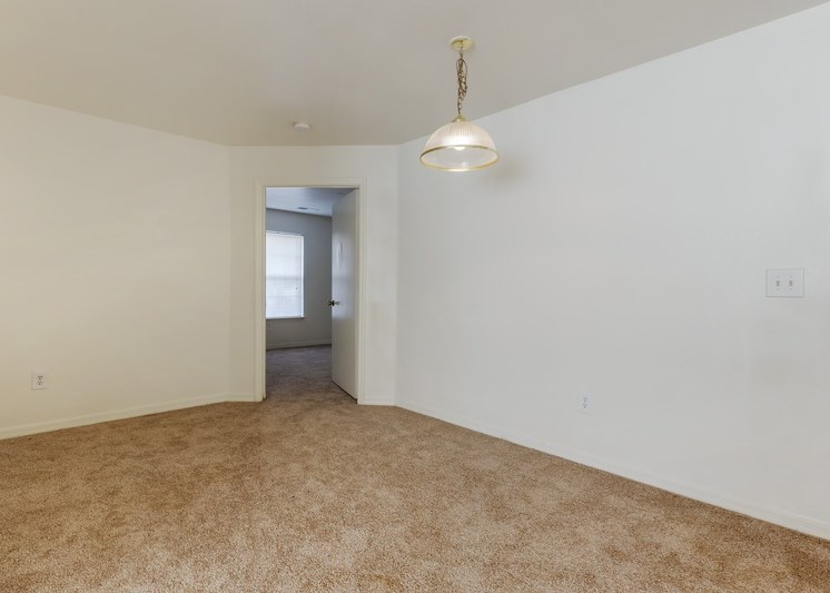 Dining room with tan carpet, white walls, and a light fixture