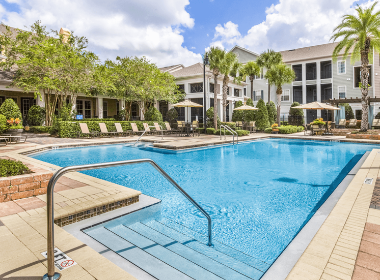 Swimming pool with lounge seating surrounded by palm trees and apartment building exterior in the background